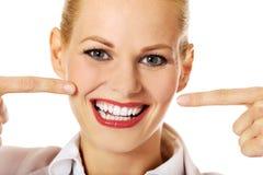 指向她愉快的微笑的女商人 库存照片