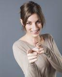 指向她的在前景的微笑的妇女手指指责有罪的某人 库存图片