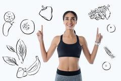 指向她的手指的正面妇女,当考虑新鲜蔬菜时 库存照片