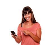 指向她的移动电话的友好少妇 库存照片