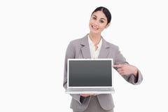 指向她的膝上型计算机屏幕的女实业家  免版税库存照片