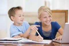 指向姐妹的大男孩家庭作业膝上型计算机 免版税图库摄影