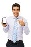 指向巧妙的电话的微笑的商人 库存照片