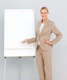 指向常设whiteboard的女实业家 库存图片