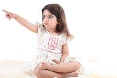 指向年轻人的逗人喜爱的女孩 免版税图库摄影