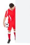 指向广告牌的足球运动员 免版税库存照片