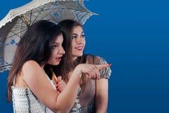 指向微笑的二伞在妇女年轻人之下 免版税图库摄影
