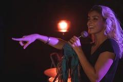 指向快乐的女歌手,当执行在夜总会时 免版税图库摄影