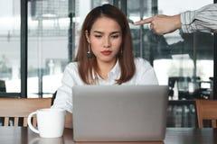 指向急切被注重的亚裔女商人的恼怒的上司的手在办公室 免版税库存照片