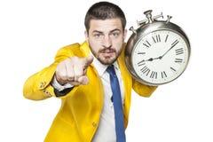 指向您的商人,在他的手上拿着一个时钟 免版税库存照片