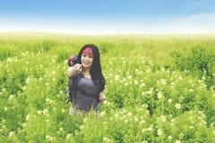 指向您的美丽的背包徒步旅行者花田的 库存照片