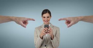 指向愉快的女商人的手使用她的电话反对蓝色背景 图库摄影