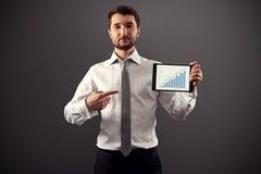 指向成长曲线图的严肃的商人 免版税库存照片