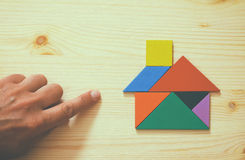 指向房子的人的手做由七巧板难题 图库摄影