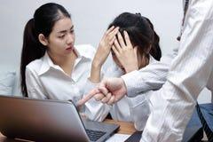 指向手指和责备年轻亚裔雇员的恼怒的男性上司的手在办公室 库存照片