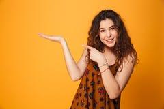 指向手指的一个微笑的卷发的女孩的画象  库存照片