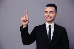 指向手指的一个微笑的商人的画象  免版税图库摄影