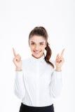 指向手指的一名微笑的年轻女实业家的画象  免版税库存图片