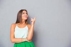 指向手指的愉快的逗人喜爱的妇女  免版税图库摄影