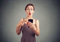 指向手机的惊奇滑稽的看的妇女 免版税库存照片