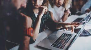 指向手的少妇膝上型计算机显示 年轻工友队在夜办公室  水平 蠢材 免版税库存照片