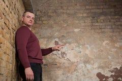 指向拷贝空间的人 红色套头衫指向的人去,当站立以剥的墙壁为背景时 免版税库存照片