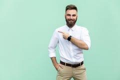 指向拷贝空间的商人 有胡子的英俊的年轻成人人在看照相机的白色衬衣和指向去,当stan时 图库摄影