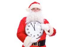 指向时钟的亲切的圣诞老人,隔绝在白色背景 免版税库存图片