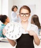 指向时钟的可爱的学生 免版税库存图片