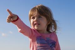 指向有他的天空的手指背景的特写镜头画象逗人喜爱的孩子 免版税库存图片