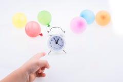 指向有气球的手一个闹钟 免版税库存图片
