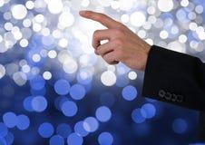 指向有闪耀的轻的bokeh背景的手 库存照片