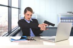 指向枪的女实业家坐计算机的膝上型计算机绝望和被注重的书桌 免版税库存照片