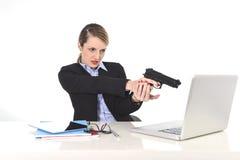 指向枪的女实业家坐计算机的膝上型计算机绝望和被注重的办公桌 图库摄影