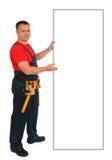 指向某事在一个空白的广告牌的一名愉快的白种人建筑工人的全长画象 微笑的英俊的水管工 免版税库存照片