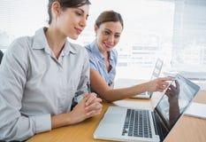 指向某事的女实业家在同事的膝上型计算机 库存图片