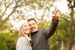 指向某事的微笑的年轻夫妇画象  免版税库存图片