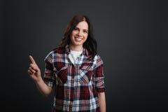 指向某事的正面聪明的妇女与她的手指 免版税库存照片