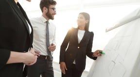 指向标志的女实业家在介绍的flipboard在办公室 免版税库存照片