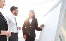 指向标志的女实业家在介绍的flipboard在办公室 库存图片