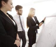 指向标志的女实业家在介绍的flipboard在办公室 免版税库存图片