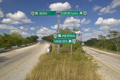 180指向梅里达和坎昆,尤卡坦半岛的收费公路的高速公路标志 免版税库存照片