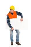 指向横幅的微笑的建筑工人。 免版税库存照片