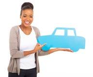 指向汽车标志的非洲妇女 免版税库存图片