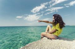 指向海洋horizont的美丽的女孩 免版税库存照片
