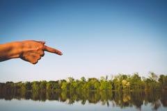 指向湖的手在阳光下 库存图片