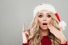 指向滑稽的圣诞节的妇女  在圣诞老人帽子的模型 库存照片
