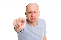 指向照相机和微笑的恼怒的秃顶的人 免版税库存图片