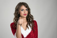 指向照相机的正面友好的年轻圣诞老人帮手女孩选择您 免版税库存照片