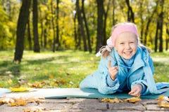 指向照相机的笑的小女孩 免版税库存图片